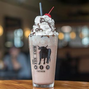 Photograph of a Spiked Milkshake with whipped cream and chocolate drizzle.